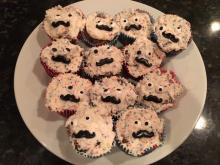 A plate containing a dozen cupcakes. The cupcakes are covered in fun-fetti icing, and decorated with candy eyeballs and moustaches to look like faces. Each cake's eyes and faces look sightly different, giving each one a unique expression, while appearing to look in different directions.